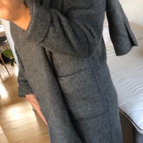 Monki frakke i uld og polyester. Det er en STOR small - jeg er en medium og den er overside til mig.   Frakken lukkes med knapper på midten. Jakken har et påsyet halstørklæde