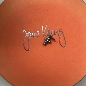 Korsvedhæng fra Jane Kønig med 6 brillanter i mat, rhodineret sterlingsølv. Korset består af små sammensatte kugler med brillantslebne diamanter på 0,005 carat. Det måler 8 mm længden og 6 mm i bredden.   Brugt enkelte gange og fremstår som nyt. Nypris: 1.500 kr. Sælges for 700 kr.