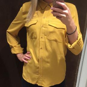 Brugt 1 gang. Lækker fed karry gul skjorte med ærmer der er smurt op. De kan også smøres ned hvis det ønskes. 3/4 ærmer.  Ingen pletter.