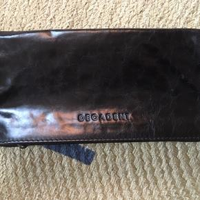 Fin, sort, skinnende pung i læder fra Decadent. Den er aldrig brugt og opbevaret i stofpose.   Nypris: ca. 799 kr.  Pris: 200