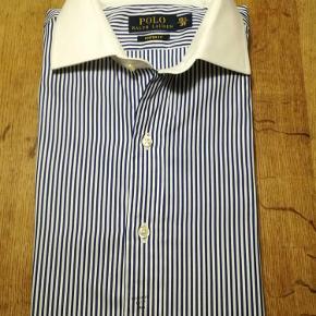 """Varetype: Skjorte Størrelse: 39 Farve: Se foto Oprindelig købspris: 1100 kr.  Super klassisk skjorte fra Ralph Lauren... Helt ny. Skjorten kan også bruges med manchetter, og et meget smart sæt medfølger. Jeg kæmpede lidt med farverne på billederne. De er lidt """"gullige"""" i det, men skjorten fremstår i klart hvid og marineblå.  Se også mine andre annoncer på kvalitetstøj. Eton, Stenströms, Armani, Prada, J.Lindeberg, Yves Saint-Laurent, Louis Vuitton, Birger Christensen, D&G, Tommy Hilfiger, Sand, Hugo Boss, Lyle & Scott, Ralph Lauren, Levis, Henry Lloyd, Peak Performance, Alberto, Y3, Napapijri, osv."""