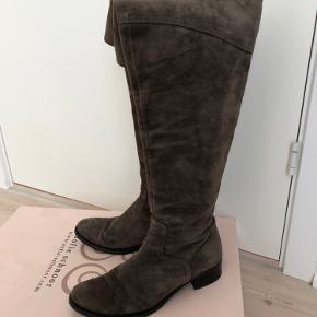 Langskaftede støvler i ruskind med overknee (der kan foldes ned).  Farven er brun (Taupe).  Der er et par små pletter/mærker enkelte steder på ruskindet, men ikke noget, man lægger mærke til.