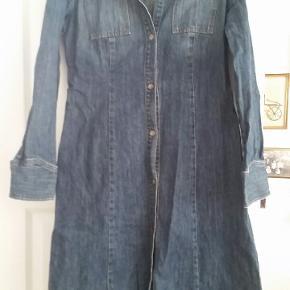 Flot lang frakke i mørk denim med tryk knapper. Tilpas tynd til at man også kan bruge den som en lang kjole på en lidt køligere dag.