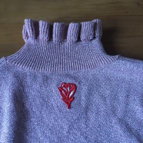 Virkelig skøn Shrimps uldsweater med glimmer og flæsekant. Den er lidt lille i størrelsen så en S kan helt sikkert også passe den. Giv et bud!
