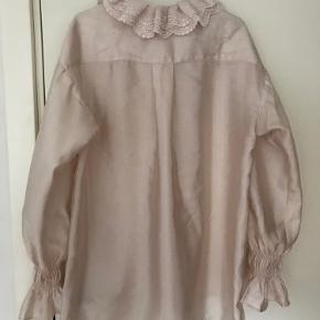 Har et lille mærke foran på blusen (se billede 3), men ikke noget man ligger mærke til hvis man ikke ved det er der.