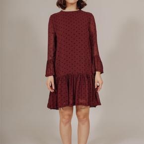 Klassisk kjole fra Ganni i den smukkeste rødbrune farve. Kjolen har et fint skørt og trumpetørmer med trekvart ærmer. Kjolen lukkes med en lynlås i ryggen. Brug med et par sneaks og en læderjakke for et cool look. Kan snildt bruges over bukserne i samme stof.  Se min anden annonce.  Str 34 100% viscose Normal pasform Maskinvask ved 30 grader  Aldrig brugt og med prismærke. Nypris 999,- Bud fra 450,- plus porto.  #secondchancesummer