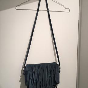 Skuldertaske med frynser i ruskind  Petroliumsfarvet taske med frynser i ruskind og detaljer i læder og lynlås. Lille indvendig lomme med lynlås. Lidt slid i hjørnerne (se billede).  Mål:  25x16cm Rem længde: 60cm (kan gøres ca. 5cm kortere i hver side)  Fra dyre- og røgfrit hjem  💃🏽