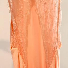 Model: Willow  Elegant lang kjole fra Samsøe & Samsøe. Kjolen har smalle skulderstropper og læg foran samt smuk blonde bagpå. – Vævet, stum kvalitet – Høj, rund hals foran – Lukkes med hægte og malle i nakken – Skjult lynlås bagpå – Lille slids i kanten forneden bagpå.   Kun brugt 1 gang.