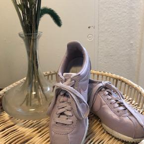 Cute Nike sneakers i blomme / lyserød shiny tekstil. Skoene er brugt få gange de har dog lidt snavs, som muligvis godt kan forsvinde med en rengøring. Dejlig lette og bløde at gå i. Sælges da jeg ikke får dem brugt - bud er velkomne 😊 måler 23cm
