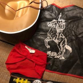 Komplet cowboy udklædning. Str. 104. Består af: Vest m frynser og badges. Hestetryk på ryggen. Bælte m patronpynt Blød, brun hat m stjerne Tørklæde m velcrolukning.  Repareret revne i hatten. Røgfrit hjem.