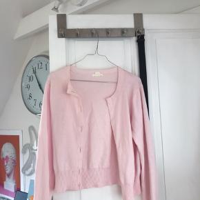 """Lyserød """"cropped"""" cardigan fra H&M, hvor knapperne er taget ud. Den kan derfor ikke lukkes."""