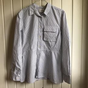 """Helt ny skjorte fra Wood Wood, str. 38. Hvid med blå striber. Har aldrig været brugt, sælges da den er for stor til mig.  Modellen hedder """"Nicole Shirt"""". Nypris var 1200 kr.   Fri fragt i dag!  Bytter ikke. Prisen er fast. Kan sendes med DAO eller hentes i Gladsaxe😊"""