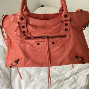 Tasken er en balenciaga city med en flot lyserød/koral farve, rigtig godt til en som ikke bare vil have standart sort! Den har en lille smule slid på hjørnerne, men ellers er den i helt perfekt stand. Næsten ikke brugt. Der er spejl og støvpose med til tasken og den opbevares i øjeblikket i en Louis Vuitton æske, som kan følge med. Jeg har ingen kvittering men har autoritets kort og ledderprøven som følger med.    Jeg bytter IKKE og prisen er fast  Kan ses eller købes på Vesterbro