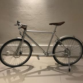 Herrecykel fra Biomega, 50 cm stel, 7 gear. Velholdt og fremstår som ny. Altid stået inde. Dansk kardan-cykel i sølv metal med brunt håntstukket læder på sadel og styr. Forsikringsgodkendt lås. Passer til en person på 159-180 cm.