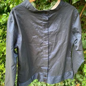 Skjorten har ikke for og bag - den kan vendes som man vil! Dvs. enten med knapper til midt på eller helt gennemknappet med skjult lukning. Selvom stoffet er polyester er den meget behagelig og desuden løs i pasformen.