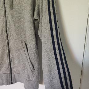 Adidas hættetrøje i grå, med mørkeblå striber ned langs ærmerne. To lommer foran og lynlås.  Er både til drenge og piger