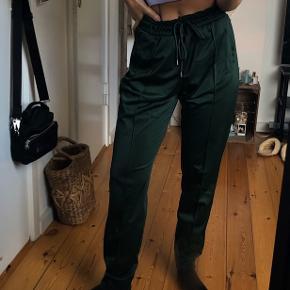 Lækre 'joggers'/bukser fra Monki i mørkegrøn. 100% polyester - satin look. Næsten ikke brugt