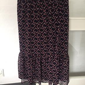 Printet nederdel med elastik i taljen og flæse forneden.  Str. 34 men kan også passe en str. 36 Kun brugt få gang så standen er rigtig fin.