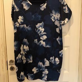 Super flot bluse i lækkert blank stof. Ryggen er ensfarvet mørkeblå. Forstykket er blankt mørkeblå med blomster i hvid og lysere blå.  Byd :-)