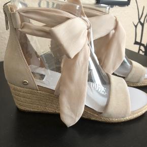 Str 40, sålen måler ca 26cm   Superfine sko med kilehæl fra UGG AUSTRALIA. De højhælede sko er fremstillet i ruskind og har en fin dekorativ sløjfe rundt om anklen. – Lynlås ved hælen Hælhøjde: 5 cm Plateau: 2 cm.  Nypris 969kr pr par  Mp 700kr + fragt pr stk + ts gebyr  KØB BEGGE PAR : 1000kr + fragt + ts gebyr