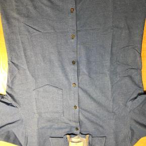 Smart skjorte/bluse med krave i str m, sælges. Den lukkes med knapper og har korte ærmer med opsmøg. Den er kun brugt en gang til konfirmation, så er så pæn og god som ny. Farven er flot blå-meleret og den klæder bare skjorte/blusen enorm godt. Farven ses rigtig og bedst på foto 2 ved str.  Iklædt denne bluse er man pæn og smart velklædt.