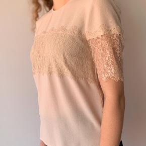 Sød t-shirt med blondedetaljer. Farven er rosa/beige.
