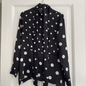 Super fin sort/hvid prikket skjorte/bluse med bånd detalje i halsen. Kan også styles som en sløjfe bagpå. Brugt få gange men desværre er der gået en tråd foran - ses dog kun helt tæt på.  Sender hver onsdag og lørdag 👉🏻 📦