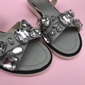 """🛍 Benyt KØB-NU funktionen ved køb 🛍  💜💜💜💜💜Nedsat pris💜💜💜💜💜  Zara Woman """"Statement"""" sandaler i str. 38 i gråt skind prydet med store faux ædelstene.   Minder om stilen fra miu miu.   Købt for 69,95 EUROS. Prisen var lidt højere herhjemme i DK.   Fra spring/sommer """"14 kollektionen.  Ægte læder   Aldrig brugte - prismærke sidder på.  Længde på grå indvendig sål: 24,5cm Længde på hvid sål under sko: 25,5cm"""
