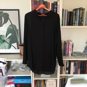 Fin sort skjorte i let transparent materiale med åben ryg. Har selv købt den brugt og aldrig brugt den☺️ passer en 38/40☺️