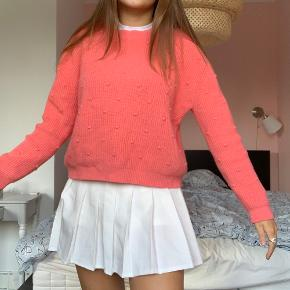 Koral/pink/lyserød sweater med fine detaljer fra MANGO.