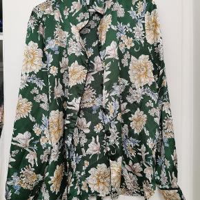 """Lækker og flot skjorte. Stoffet har nogle snore (se billeder) ikke noget man ser. Knappen er også slidt. Derfor den billige pris. Der er """"binde Bælte"""" Med til skjorten som er i samme stof og mønster."""