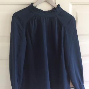 Marineblå skjortebluse med høj hals og lange ærmer. Fejler intet. Skulder og ned 64 cm. Brystvidde 51*2 cm.