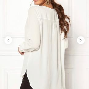 Bluse model DYNELLA i hvid  - Loose fit - 100% Polyester - Lange ærmer - Knappestolpe - Længere på ryg - Let kvalitet.  Sælger også i andre farver, samme model.