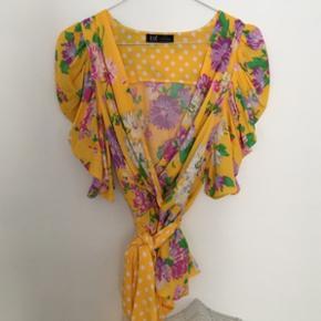 Smuk gul blomstret sommerbluse med puf ærmer og bindebånd. Aldrig brugt, passer også en xs