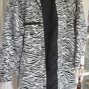 Fantastisk flot regnfrakke regnjakke med aftagelig hætte, quiltet foer, inderlomme, lækre detaljer med bla. 2 lynlåse forneden bagpå, som kan lynes op, så man nemmere kan cykle med den på. Vandsøjletryk: 3000 Foer:100% polyester 100% Pu.. Str xxl Zebra dvs helt sort og hvid. Nypris 1500. Sender med Dao til 45. Pris er uden porto