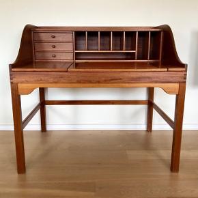 Unikt Andreas Hansen skrivebord i mahogni. Overdel med otte rum og tre skuffer. Opklappelig skriveplade delt i to - den store skriveflade beklædt med læderskind. Tegnet for Hadsten Træindustri A/S. Fremstår med minimale brugsspor.Vurderet til ca. 9.000,- Sælges for 7.000,-  Kan leveres i og omkring 6700.  Mål: 112 cm bred 82 cm dyb Skriveplade 54x107 cm Skrivehøjde 74 cm Total højde 103 cm
