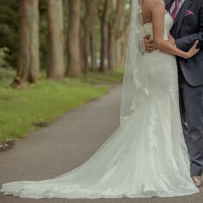 Brudekjole fra Karim Design. Jeg har selv designet kjolen i august 2018 hvor den oprindelige pris var 17.000 kr. Den er brugt en enkelt gang til mit bryllup. Kjolen er lavet med et korset og kan derfor snørres ind på ryggen fra en størrelse XS til Medium. Den er syet efter min højde (1.68 cm). Kjolen er speciel da der er lagt et lag champagne-farvet silke under den hvide blonde, hvilket gør at blonden ses tydeligere, samt giver et fint spil i kjolen. Slæbet kan sættes op med en knap bag på kjolen, så den er nem at have med at gøre og kan danses i hele natten. Kjolen har været til rens lige efter brug og fremstår derfor som ny.  Kjolen kan sys om eller få detaljer tilføjet, som f.eks. ærmer, hos Karim Design.