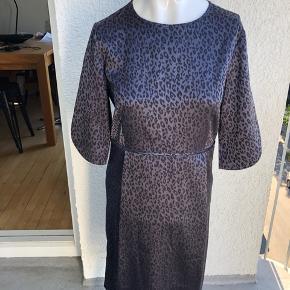 Flot kjole med leopardprint. Det er formentlig en kollektionsprøve, for der er ingen mærker i, som viser størrelsen eller materialet. Der er lidt stretch i stoffet. Den er str. M/38, men se også mål. Mål er: Brystmål: ca. 2*47 cm Længde: ca. 96 cm Den er aldrig brugt, kun prøvet på :-) Min. pris 150 plus porto