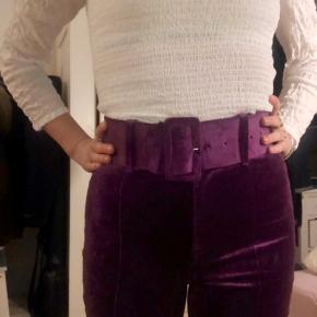 Super skønne lilla aubergine farvede højtaljede bukser i velour med bælte så du får en flot talje. Lynlås og indvendige knappe lukning. Perfekt til fest og farver eller til en dejlig skør hverdag. Passes af XS - 34, i hvert falder lidt for små til mig :-)))