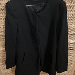 Fin frakke fra ZARA med skulderpuder og lynlås, som er gemt lidt væk.  Har lomme, men den ene lomme er der et stort hul i, men burde kunne syes Byd gerne
