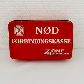 Zone-Redningskorpset blev dannet i 1930 af udbrydere af Falcks Zone-Brand-Væsen. Falck og Zonen udkæmpede en hård konkurrence, der for Zonens vedkommende betød udvikling af innovative projekter som f.eks. flyve-ambulance-tjenesten. I 1963 købte Falck aktierne i Zonen og korpsene bar navnet Falck-Zonen frem til 1977. Fra 1977 er korpsene alene markedsført under navnet Falck. Her sælges en original forbindskasse af metal med indhold. Længde: 18,5 cm Bredde: 11,3 cm Højde: 4,2 cm