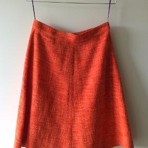 Smuk A-nederdel i strukturvævet stof. Nederdelen har orange foer i bomuld og fine lilla stropper, der gør det enkelte at hænge den i skabet. Aldrig brugt, kun hængt i skab i røgfrit hjem uden dyr!