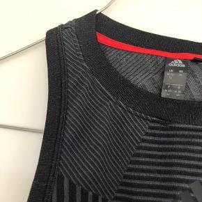 Den lækreste sports top fra Adidas i str. M. Den har aldrig været brugt. Nypris 500kr.   Den er lavet af 75% polyester, 18% polyamid og 7% elastik.