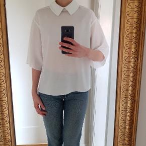 """Hvid tunika i god stand. Eneste """"brugsmærke"""" er bagsiden, hvor der er klippet et stykke af stoffet for at skabe et asymmetrisk look (se billeder)."""