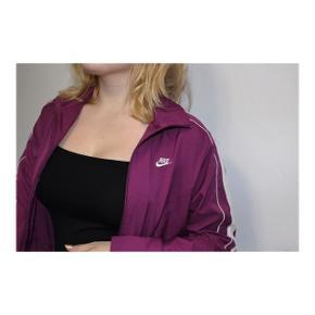 Lilla Nike jakke med hvide detaljer i størrelse medium.