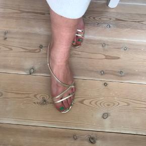 Guld-farvede sandaler med stropper og lille kitten-heeel. Skoene er en UK 6, men jeg bruger str. 40. Grundet den justérbare strop, kan både en str. 39 og 40 passe de sandalerne, som også har et vintage udtryk.