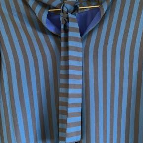 Meget flot skjorte/bluse fra Mads Nørgaard. Klar blå/sort. Bindebånd i nakken. 100 % polyester. Brugt få gange - aldrig vasket, kun luftet.