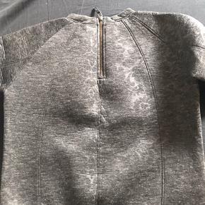 Kraftig bluse med lynlås i nakken og 3/4 ærmer. Fin stand - næsten ikke brugt.