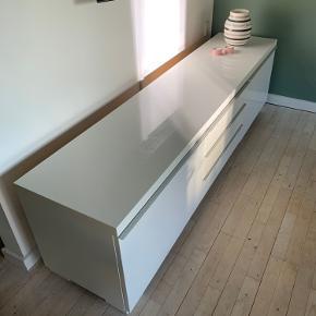 Jeg sælger denne tv bænk, da jeg har købt nyt. :)  Der er kommet et lille hak på den (se sidste foto), det er ikke noget man lægger mærke til hvis ikke man ved det. Den fremstår god, men brugt og sælges derfor billigt.   Mål: 180x41x49 cm  https://www.ikea.com/dk/da/p/besta-burs-tv-bord-hojglans-hvid-30269129/  Afhentes i Valby. :)  Pris: 450kr.