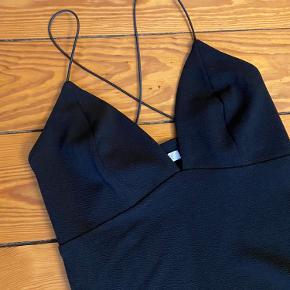 Stilet stram sort kjole med kryds på ryggen og flot udskæring.